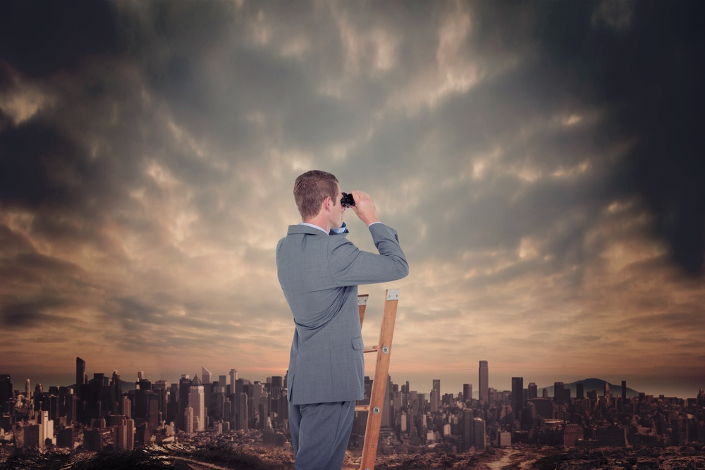 Businessman looking on a ladder against dusty path leading to large city.jpeg