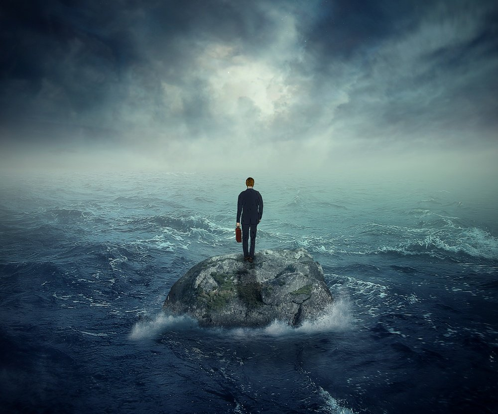 Failure crisis concept and lost business career education opportunity. Lonely young man on a rock cliff island surrounded by an ocean storm waves .jpeg
