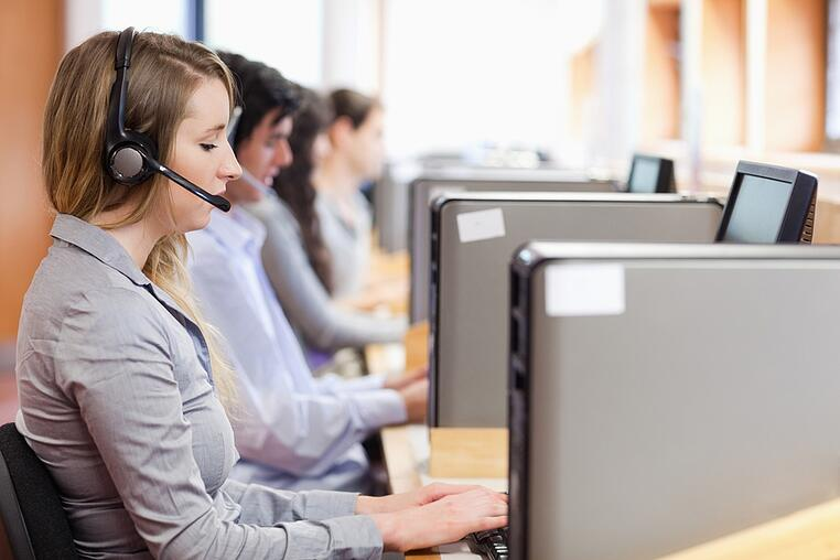 Operators using a computer in call center with the camera focus on the foreground.jpeg